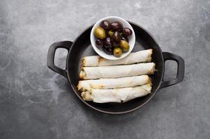 Käsebrötchenteller mit Oliven in einer schwarzen Pfanne serviert