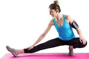 fit Frau streckt sich auf Trainingsmatte foto