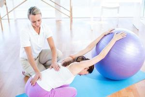 Trainer hilft Frau mit Gymnastikball