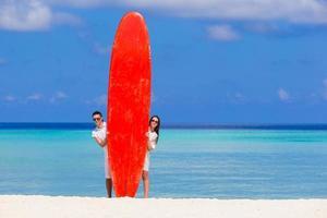 junges Paar mit rotem Surfbrett am weißen Strand