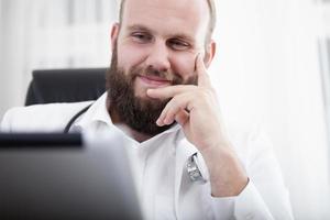 lachender arzt gehört etwas auf seinen Tablet-Computer foto