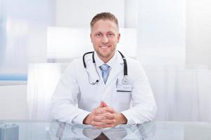 lächelnder Arzt oder Berater, der an einem Schreibtisch sitzt