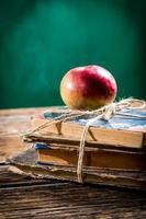 alte Bücher und Apfel auf der Schulbank