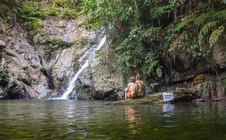 fröhliches Paar, das Flussbad durch Wasserfall genießt