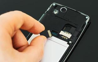 männliche Hand, die Mikro-SD-Karte in Mobiltelefon einführt. foto