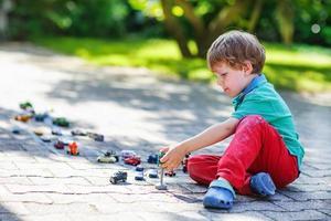 kleiner Kleinkindjunge, der mit Autospielzeug spielt foto