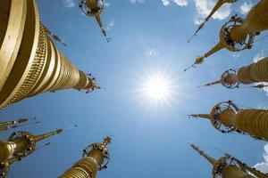 Myanmar goldene Stupas auf einem blauen Himmel mit Sonne