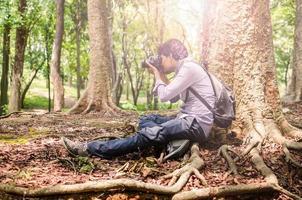 Fotograf, der Fotos macht, die unter einem großen Baum sitzen