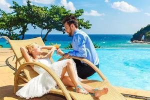 glückliche Braut und Bräutigam genießen einen Cocktail am Pool unendlich foto