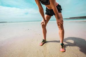 sportliche junge Frau, die nach dem Laufen am Strand ruht foto