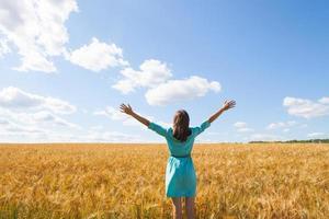junge Frau, die Sonnenlicht mit erhobenen Armen im Strohfeld genießt foto