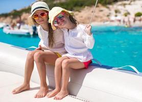 Porträt der niedlichen Mädchen, die das Segeln auf dem Boot im Meer genießen foto