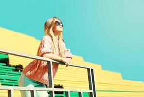 schöne Modefrau, die sonnigen Tag über blauem Himmel genießt