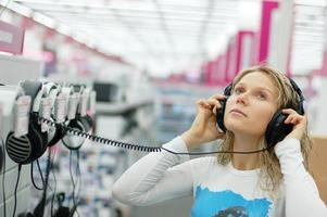 junges Mädchen, das erfreuliche Musik in einem Geschäft hört foto