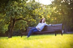 schöne junge schwangere Frau, die den Sonnenuntergang im Herbstpark genießt foto