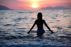 wunderschöne fit Frau Silhouette schwimmen im Sonnenuntergang. Freie Frau genießt Sonnenuntergang. foto