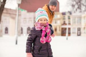 Porträt des kleinen glücklichen Mädchens genießt das Schlittschuhlaufen mit ihrem Vater