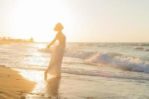 junge Frau genießt es, in der Abenddämmerung an einem dunstigen Strand spazieren zu gehen.