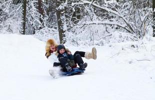 Mutter und Sohn genießen Schlittenfahrt an einem schönen Wintertag
