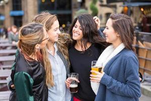 Gruppe von Frauen, die ein Bier in der Kneipe in London genießen.