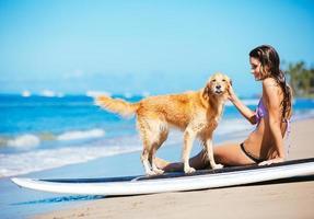 Frau, die sonnigen Tag am Strand mit ihrem Hund genießt foto