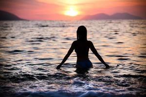 wunderschöne fit Frau Silhouette schwimmen im Sonnenuntergang. Freie Frau genießt Sonnenuntergang.