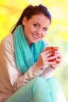 glückliches Mädchen, das im Herbstpark entspannt heißes Getränk genießt foto