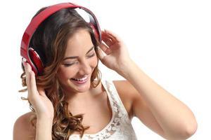 junge glückliche Frau genießt das Hören der Musik von Kopfhörern