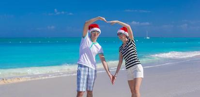 Porträt des jungen Paares in den Weihnachtsmützen genießen Strandurlaub foto