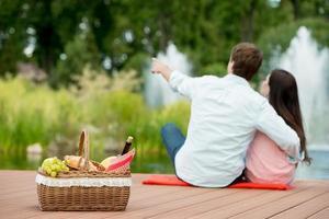 glückliches romantisches Paar, das Picknick in einem Park nahe See genießt foto