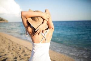 Sommermodefrau, die Sommer und Sonne genießt und den Strand spazieren geht