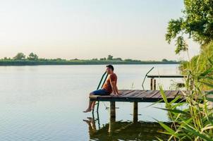 junger Mann sitzt entspannend und genießt die Aussicht vom Dock foto
