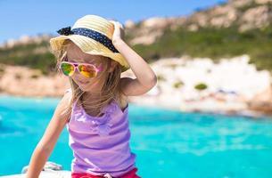 süßes kleines Mädchen, das das Segeln auf dem Boot im offenen Meer genießt foto