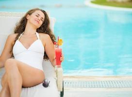 glückliche junge Frau mit Cocktail genießt das Liegen auf Chaiselongue