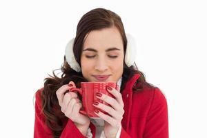 Frau in Winterkleidung genießt ein heißes Getränk Augen geschlossen