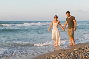 junges Paar geht gerne in der Abenddämmerung an einem dunstigen Strand spazieren