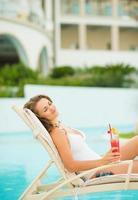 glückliche junge Frau mit Cocktail genießt das Liegen auf Chaiselongue foto