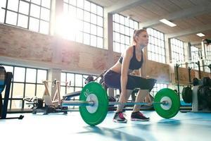 fokussierte junge Frau, die Gewichte in einem Fitnessstudio hebt foto