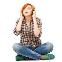 junges Mädchen genießt das Hören von Musik auf Kopfhörern isoliert auf foto