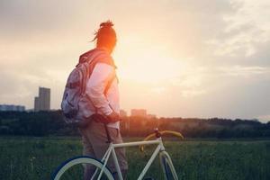 Mann mit Fahrrad auf der grünen Wiese foto