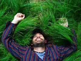 lächelnder Mann, der auf Gras liegt foto