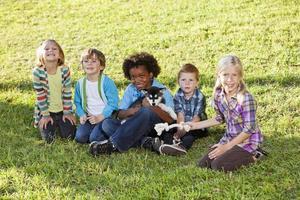 gemischtrassige Kinder, die auf Gras mit Huskywelpen sitzen foto