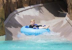 glücklicher kleiner Junge, der eine nasse Fahrt eine Wasserrutsche hinunter genießt