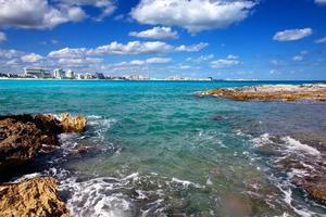 felsige Küste, Meer und Stadt in der Ferne Mexiko. cancun foto