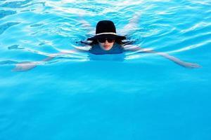 Frau in Sonnenbrille und Hut schwimmt im Pool foto