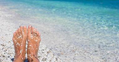 weibliche Beine mit Kieselsteinen am weißen Sandstrand