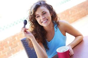 junge Frau, die gefrorenen Joghurt genießt foto