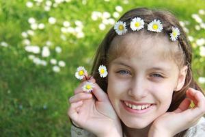 schönes Mädchen, das die Kamillenblätter genießt foto