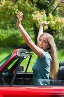 lächelnde Blondine genießt ihr rotes Cabriolet
