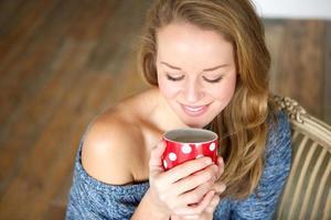junge Frau, die Tasse Tee zu Hause genießt foto